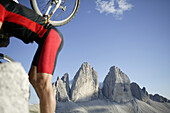 Mountain biker carrying his bicycle, Tre Cime di Lavaredo, Dolomites, Veneto, Italy