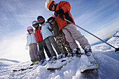 Children wearing ski helmet and ski googles standing side by side, skiing region Sonnenkopf, Vorarlberg, Austria