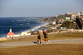 Two joggers at the park in front of castillo San Felipe del Morro, view over the north coast, San Juan, Puerto Rico, Carribean, America
