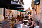 People sitting under sunshades in front of the cafe at Calle de Christo, San Juan, Puerto Rico, Carribean, America