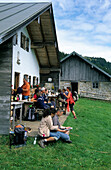 alpine hut Hofbauernalm with group of hikers on terrace, Kampenwand, Chiemgau range, Chiemgau, Bavarian foothills, Upper Bavaria, Bavaria, Germany