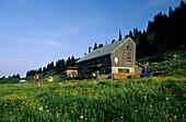 hut Riesenhütte with two mountainbikers, Hochries, Chiemgau range, Chiemgau, Bavarian foothills, Upper Bavaria, Bavaria, Germany