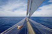 Couple relaxing in bowsprit net of sailing Cruiseship Star Flyer (Star Clippers Cruises), Bora Bora, Society Islands, French Polynesia