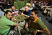 Men playing a game of chess and smoking a Shisha water pipe at an outdoor cafe near the Citadel, Aleppo, Syria, Asia