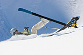Two female skiers lying in the snow after a fall, Disentis, Grisons, Switzerland