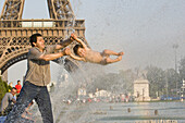 Father and son playing in the water of the fountain in front of the Eiffel Tower, Paris, France, Europe