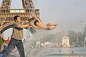 Vater und Sohn spielen am Springbrunnen vor dem Eiffelturm, Paris, Frankreich, Europa