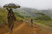 Woman walking with umbrella on track, Langila, Highland, Papua New Guinea, Oceania