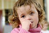 Three year old girl , looking very pensive and worried, at nursrey school