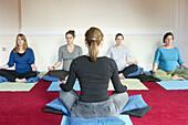 Yoga teacher sitting cross legged in front of class of four pre-natal women
