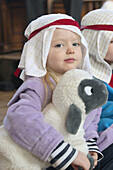 3 year old girl dressed up for a nativity play holding a toy sheep, looking into camera