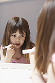 4 year old girl applying lipgloss in a mirror