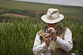 Elderly man taking a photo in some reeds by a lake, Devon, England. UK.