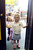 group of 2-4 year old children standing in the doorway of the classroom at nursery