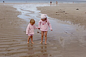 4 and 2 year old girls standing on the beach holding hands, laughing
