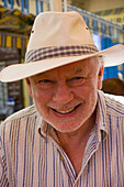 good looking 70 year old man wearing a sunhat, with a grey beard, smiling into camera ,in the sunshine