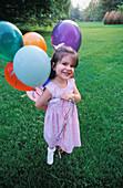 3-4 Jahre, 5-10 Jahre, Außen, Ballon, Ballons, Blick Kamera, Dunkelhaarig, Eine Person, Eins, Einzeln, einzig, Farbe, Freude, Ganzkörper, Ganzkörperaufnahme, Gesichtsausdruck, Gesichtsausdrücke, Glück, Glücklich, Kind, Kinder, Kindheit, Kleinkind, Kleink