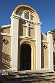 Exterior of church, arched doorway, painted stucco walls, Spanish architecture. Cabo San Lucas, Mexico