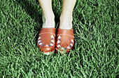 Adult, Adults, Anonymous, Clog, Clogs, Color, Colour, Concept, Concepts, Contemporary, Country, Countryside, Daytime, Detail, Details, Exterior, Feet, Female, Foot, Footgear, Footwear, Grass, Horizontal, Human, Lawn, One, One person, Outdoor, Outdoors, O