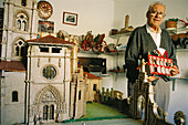 Mr. Néctor Calzada and his old farm implement miniature collection that he shows in his own home. Sasamón. Burgos province, Spain
