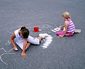 Young girls drawing on pavement with chalk. Anacortes, Skagit County. Washington, USA