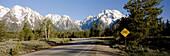 Bicycle caution sign along highway, Mt. Moran and Teton mountain range, Grand Teton National Park. Teton County, Wyoming, USA