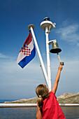 little girl ringing bell on ferryboat, croatian flag, Dalmatia, Croatia