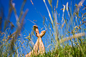 Barefoot woman lying on meadow, Upper Bavaria, Germany