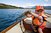 Girl (3-4 years) rowing on lake Bettmersee, Bettmeralp, Canton Valais, Switzerland