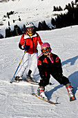 A little girl and her grandmother skiing at Flims, Graubünden, Switzerland