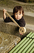 Child washing hands at Shinto shrine. Kyoto. Japan