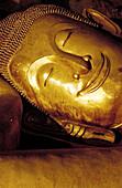 Detail, face of reclining Buddha statue in underground cave. Petchaburi, Thailand.