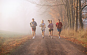 Four friends jogging on a country road