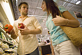 couple shopping for produce in supermarket