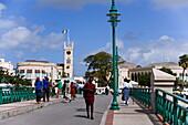 People walking over a bridge, parliament building in background, Bridgetown, Barbados, Caribbean
