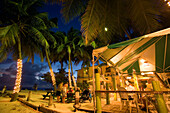 Guests in the Carib Beach Bar in the evening, Barbados, Caribbean