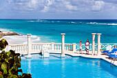 Vacationer at swimming pool of the Crane Hotel, Atlantic Ocean in background, Barbados, Caribbean