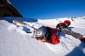 Children lying in snow, Maennlichen, Grindelwald, Bernese Oberland, Canton of Bern, Switzerland