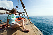 Woman sunbathing on dhow, Snorkeling and Diving Trip, Kisite-Mpunguti Marine National Park, Coast, Kenya