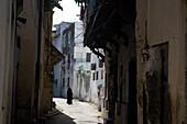Muslim woman walking through lane in Old Town, Mombasa, Kenya