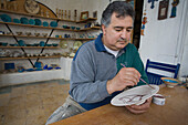 Efthymioos Symeou, ceramic artist and craftsman painting a plate, Pottery workshop, Larnaka, South Cyprus, Cyprus