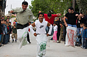 A group of men taking part in a sack race at the Easter games, Kathikas, South Cyprus, Cyprus