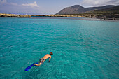 Man snorkeling in the sea during trip in a glass bottom boat with Spyros Plakides, Akamas coast, from Latsi harbour, near Polis, Cyprus