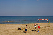 Boys and young men playing football on Salamis beach, Salamis, Cyprus