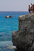 Man cliff jumping, diving from a the rock, Nissi island, Nissi beach, Agia Napa, South Cyprus, Cyprus