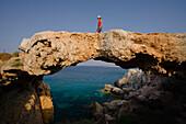 Woman walking over a natural bridge, Rocky coastal landscape at Cape Gkreko, near Protaras, near Agia Napa, South Cyprus, Cyprus