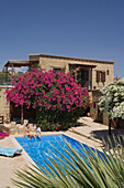 A couple sitting on the edge of the pool, Traditional guesthouse and pool, Cyprus Villages Traditional Houses Ltd., Agrotourism, Tochni, near Larnaka, Cyprus