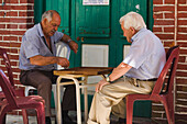 Two older men playing a game outside a cafe, coffee shop, Kafenion, Koilani, Troodos mountains, Cyprus