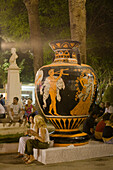 People at a Wine Festival sitting in front of a huge sculptur of a pitcher, Limassol, Cyprus