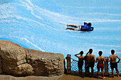 Four men watching a person on a surf board at Wild Wadi Waterpark, Dubai, United Arab Emirates, UAE